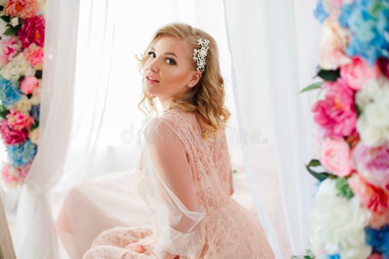 Jeune femme dans la chambre décorée des fleurs images libres de droits