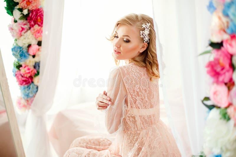 Jeune femme dans la chambre décorée des fleurs photos libres de droits