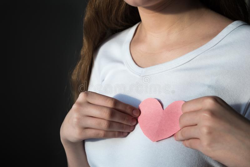 Jeune femme dans la chemise blanche tenant le coeur de papier rose contre le coffre photos libres de droits