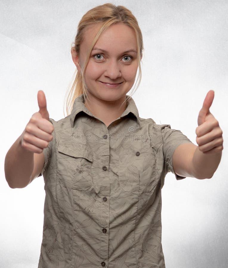 Jeune femme dans la chemise de trekking avec des pouces vers le haut du regard directement dans la caméra image stock