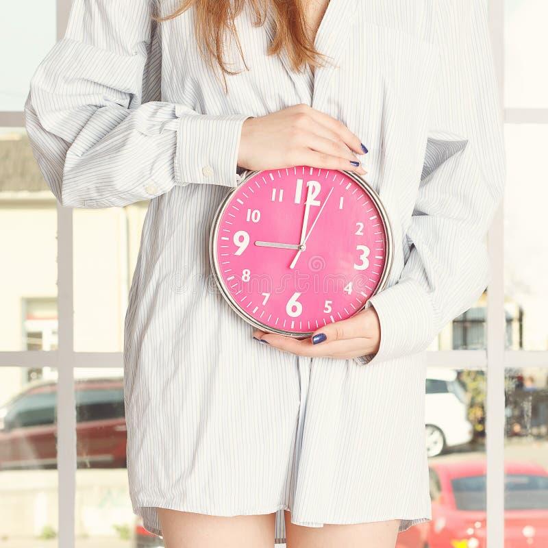 Jeune femme dans la chemise rayée tenant le réveil rose photographie stock