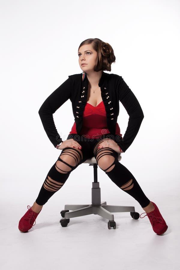 Jeune femme dans la chemise rouge, veste moderne, guêtres avec des trous, au sujet de photo libre de droits
