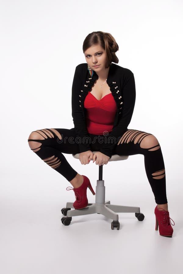 Jeune femme dans la chemise rouge, veste moderne, guêtres avec des trous, au sujet de photos libres de droits