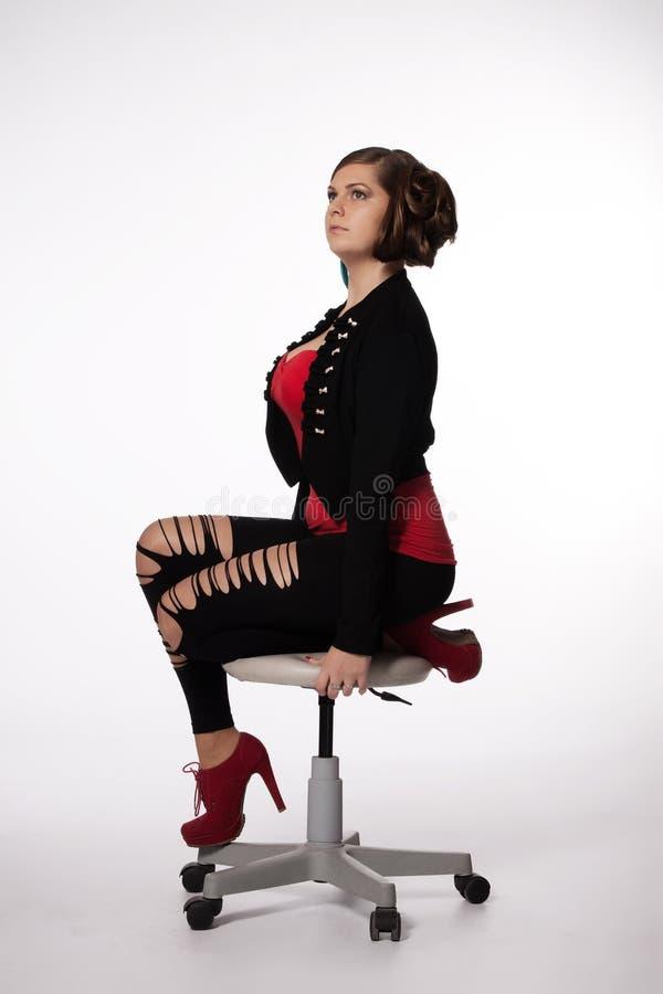 Jeune femme dans la chemise rouge, veste moderne, guêtres avec des trous, au sujet de images stock