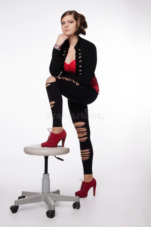 Jeune femme dans la chemise rouge, veste moderne, guêtres avec des trous, au sujet de photos stock