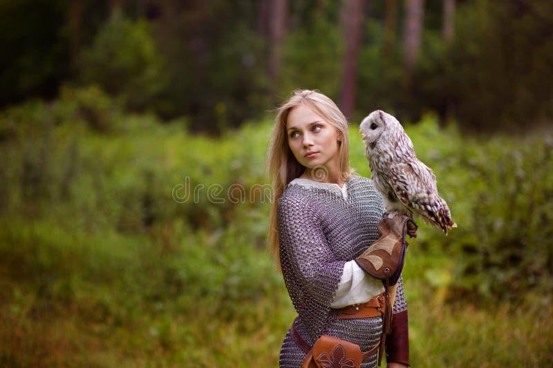 Jeune femme dans la cotte de maille avec le hibou regardant loin photographie stock libre de droits