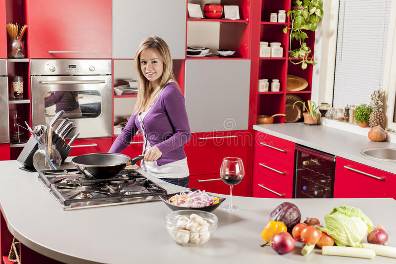 Jeune femme dans la cuisine photos stock