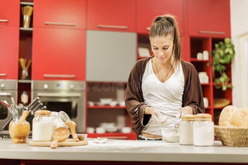 Jeune femme dans la cuisine photo stock