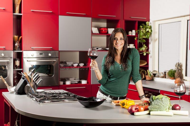 Jeune femme dans la cuisine avec la glace de vin photo libre de droits