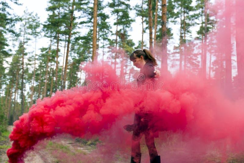 Jeune femme dans la forêt ayant l'amusement avec la grenade fumigène rouge, bombe photos libres de droits