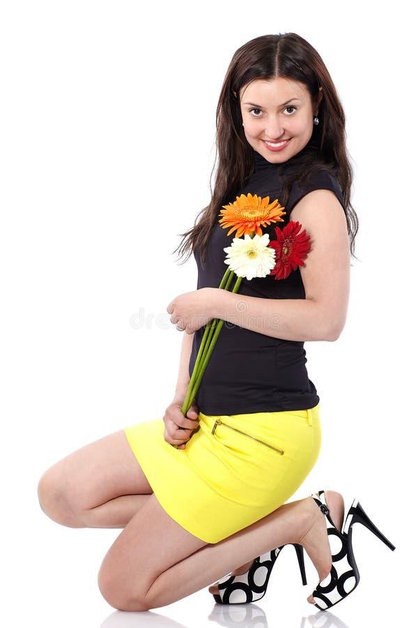 Jeune femme dans la jupe jaune courte avec des postures accroupies de gerberas dans le studio sur le fond blanc photo stock