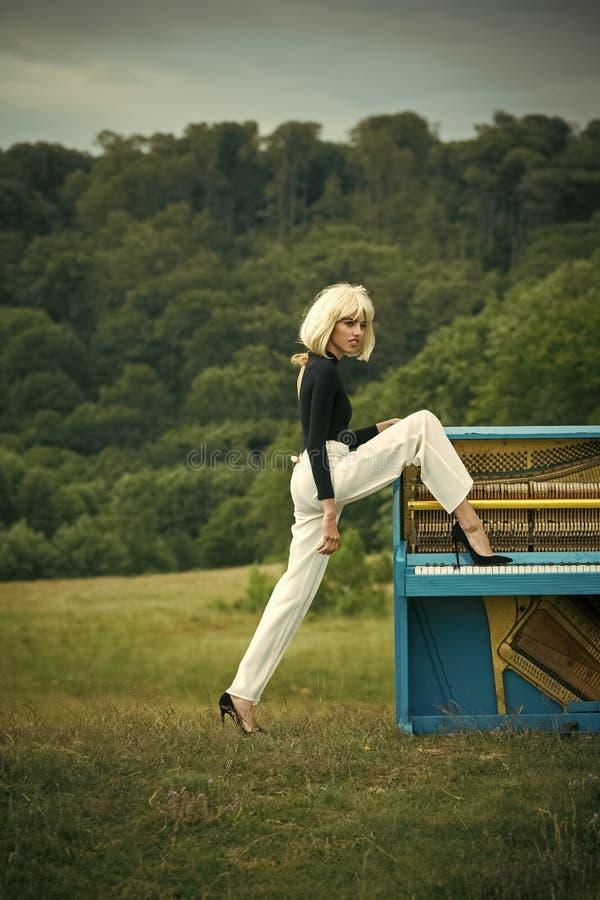 Jeune femme dans la perruque blonde jouant le piano dans le rétro intérieur de style avec la jambe dans la chaussure photos stock