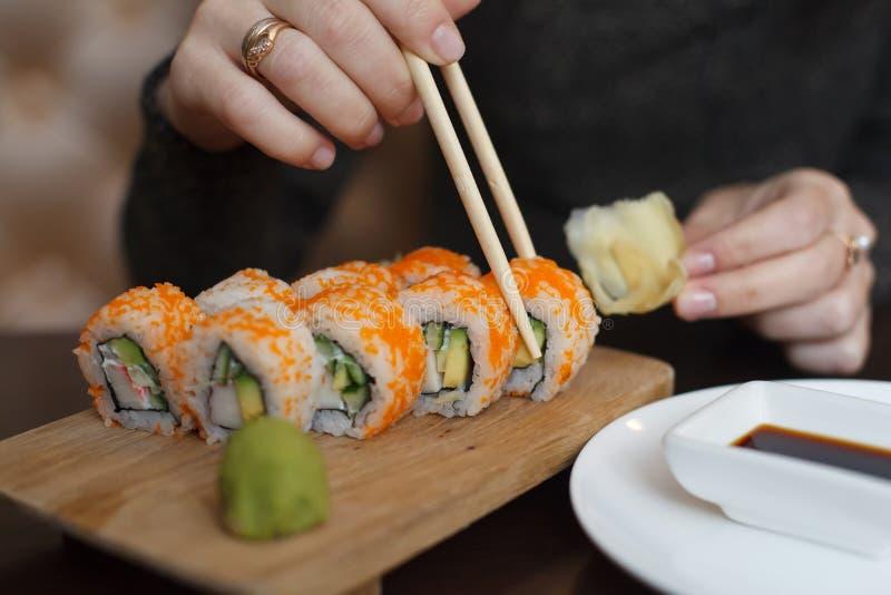 Jeune femme dans la perruque mangeant des sushi par des baguettes photos libres de droits