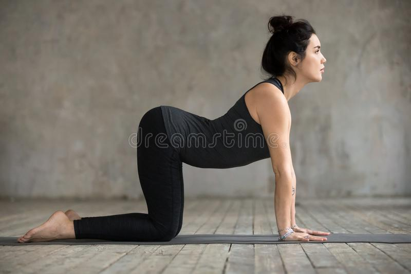 Jeune femme dans la pose de Bitilasana photo stock