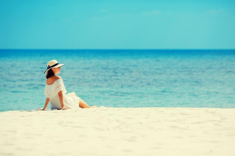 Jeune femme dans la robe blanche et le chapeau se trouvant sur le sable de la plage tropicale ayant la grande heure d'été photos stock