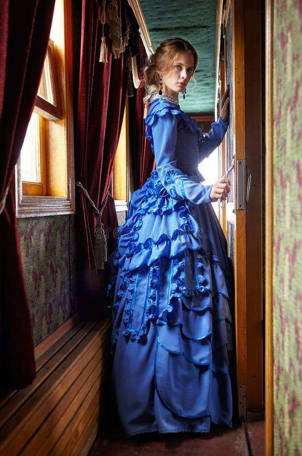 Jeune femme dans la robe bleue de vintage se tenant dans le couloir de rétro photographie stock libre de droits