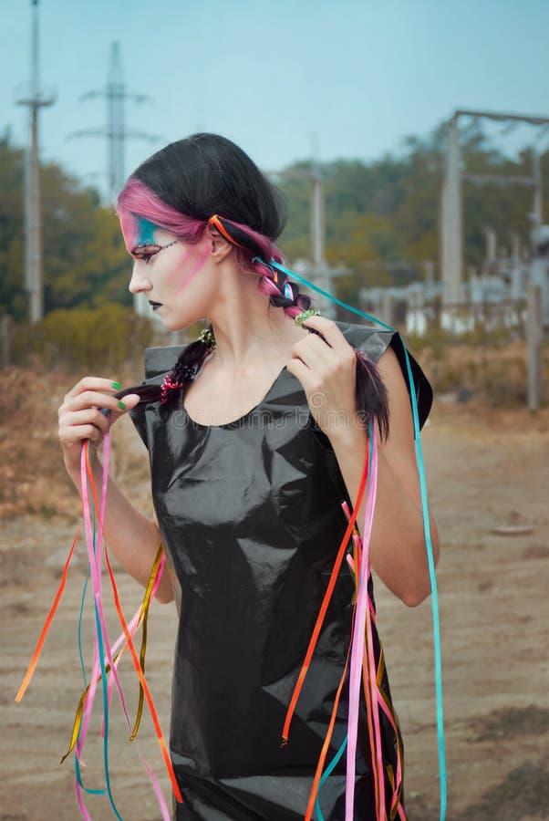 Jeune femme dans la robe de polyéthylène avec des bandes images stock