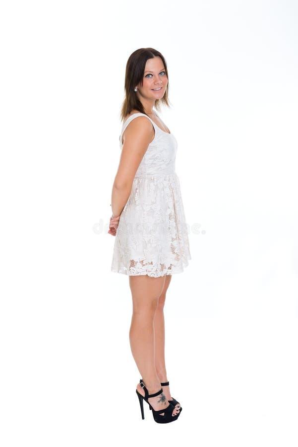 Jeune femme dans la robe et des talons hauts courts devant le backg blanc image stock