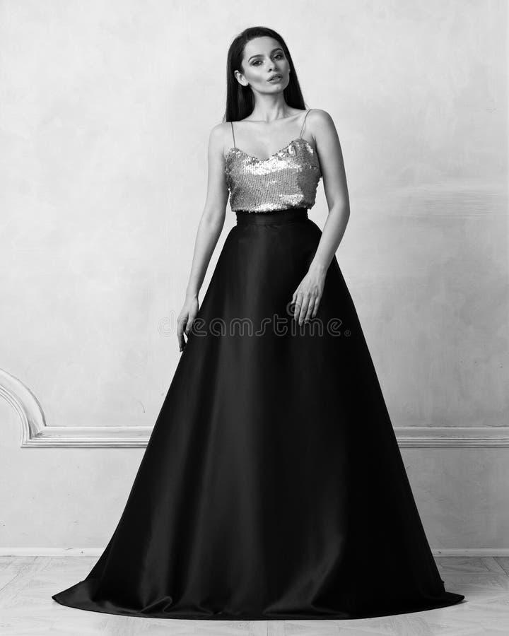 Jeune femme dans la robe formelle avec le dessus d'or de paillette et la SA pourpre images stock