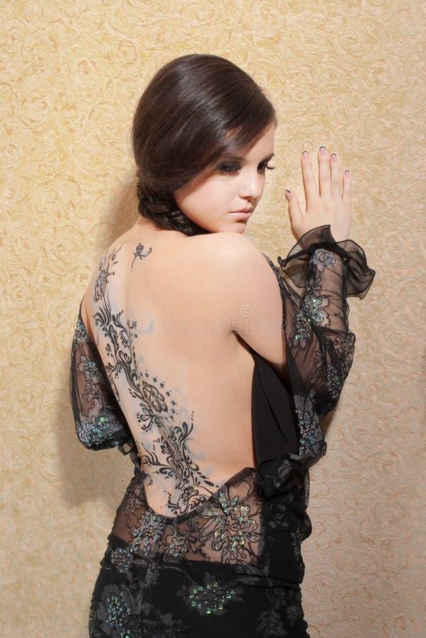 Jeune femme dans la robe noire avec l'art de fuselage photo stock
