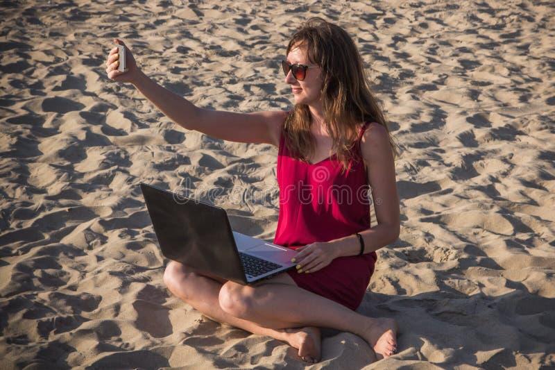 Jeune femme dans la robe rouge avec l'ordinateur et le smartphone sur le bea photos stock