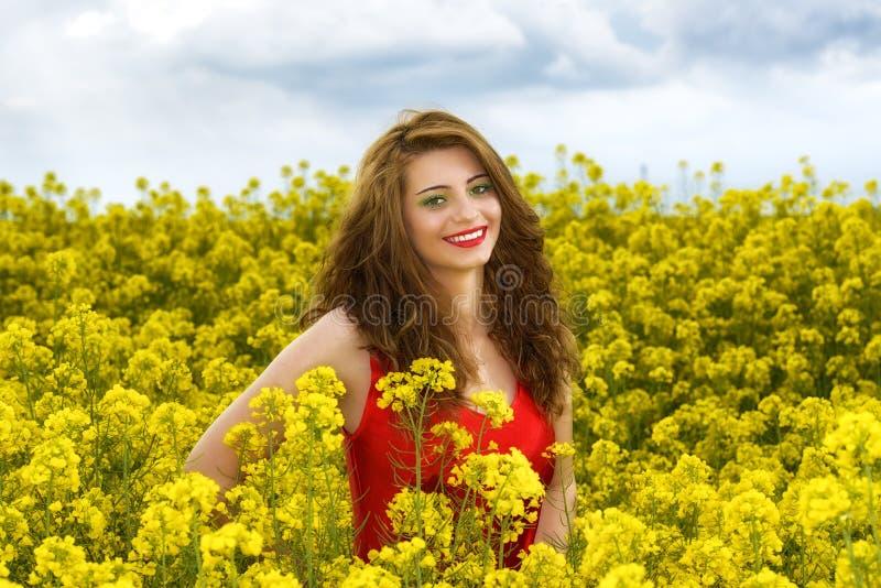Jeune femme dans la robe rouge dans le domaine jaune images stock