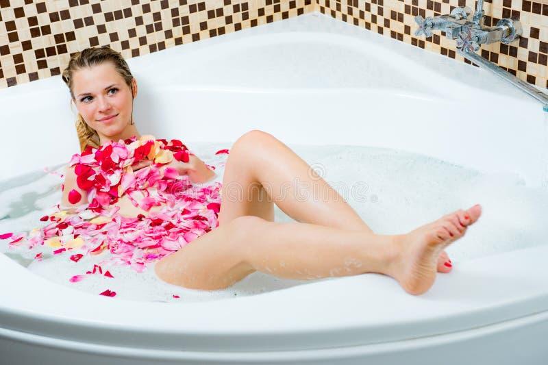 Jeune femme dans la salle de bains avec la mousse et les pétales de rose image libre de droits