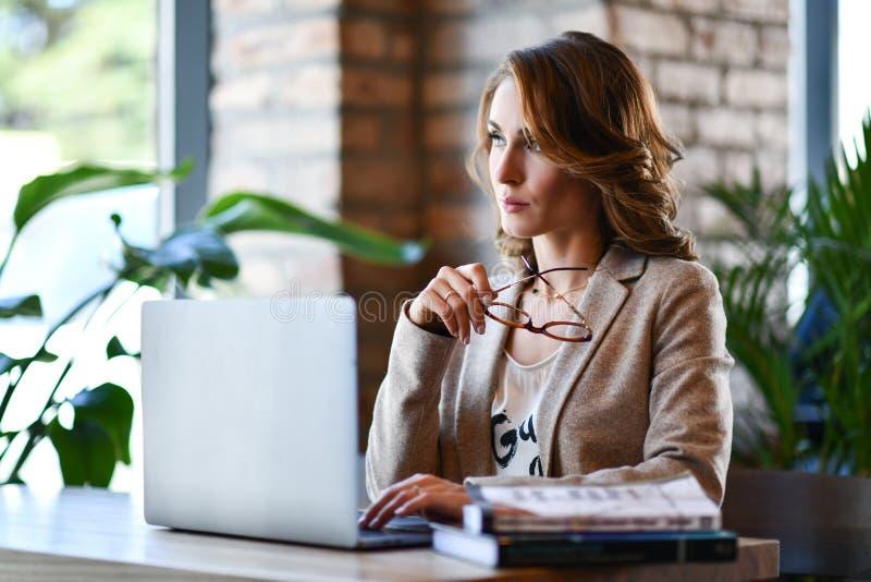 Jeune femme dans la tenue de détente futée travaillant sur l'ordinateur portable tout en se reposant près de la fenêtre en bureau images stock