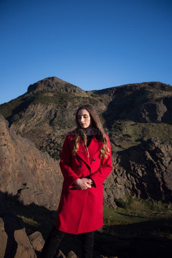 Jeune femme dans la veste rouge avec beaucoup dessus son esprit photo libre de droits