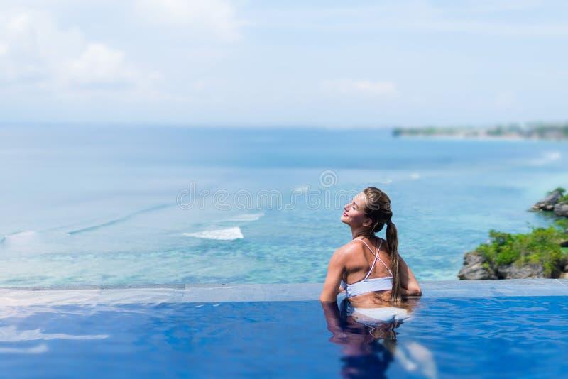 Jeune femme dans le bikini blanc appréciant un soleil dans la piscine d'infini Vacances et concept d'été photo stock