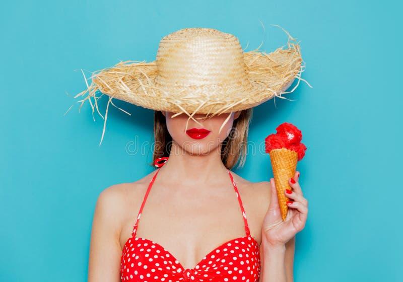 Jeune femme dans le bikini et le chapeau de paille rouges avec la crème glacée  photo stock