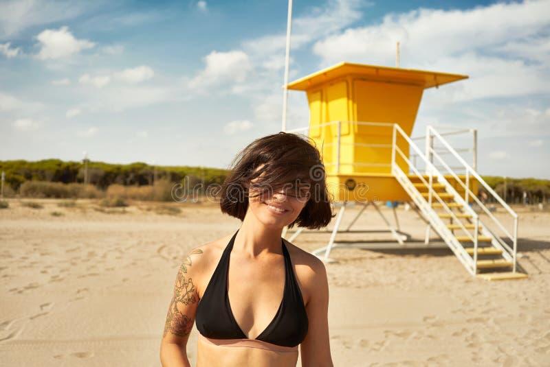 Jeune femme dans le bikini noir près d'un courrier jaune de maître nageur photographie stock