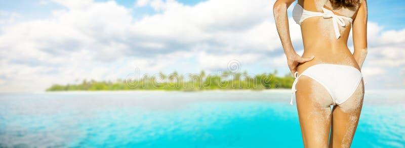Jeune femme dans le bikini regardant l'île images stock