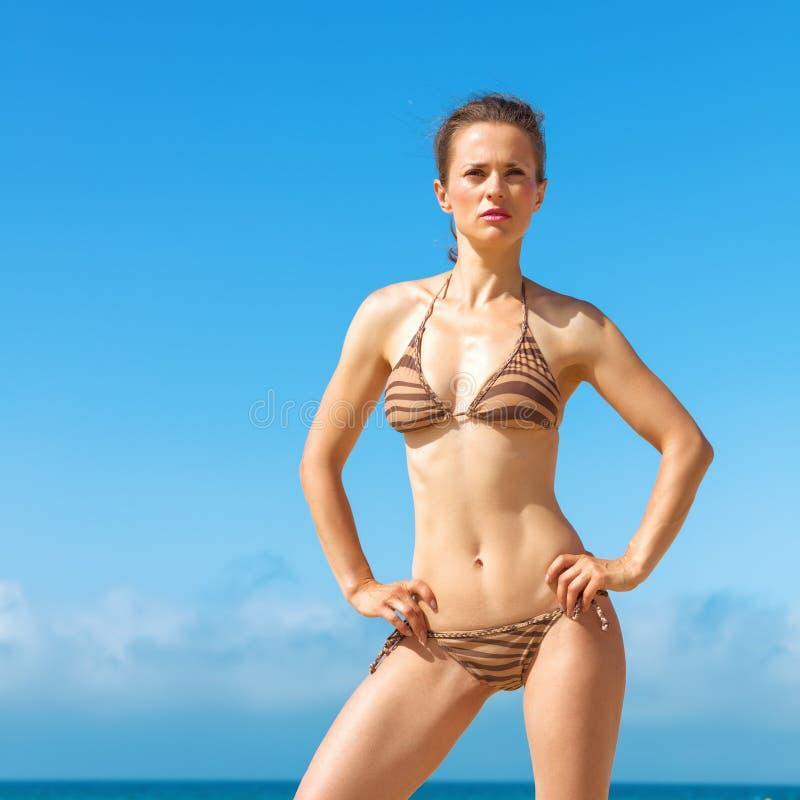 Jeune femme dans le bikini sur la plage examinant la distance photographie stock