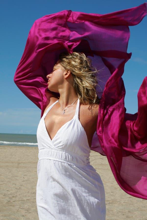 Jeune femme dans le blanc sur la plage avec osciller rouge photos libres de droits