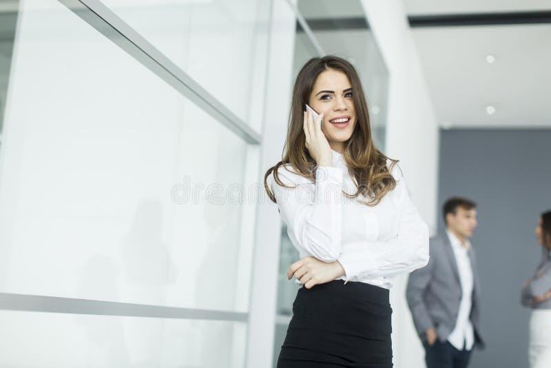 Jeune femme dans le bureau avec le téléphone portable image stock