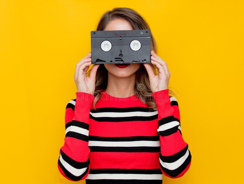 Jeune femme dans le chandail rayé rouge avec la cassette de VHS photo libre de droits