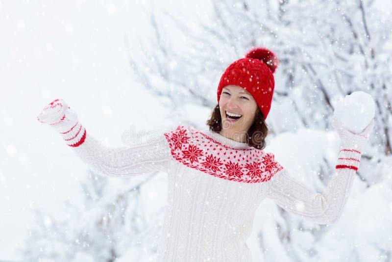 Jeune femme dans le chandail tricoté jouant le combat de boule de neige en hiver Fille dans le jeu de boules de neige de famille  image libre de droits