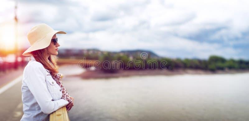 Jeune femme dans le chapeau au coucher du soleil d'automne regardant loin sur le pont photographie stock libre de droits