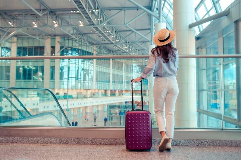 Jeune femme dans le chapeau avec des bagages dans l'aéroport international photographie stock libre de droits