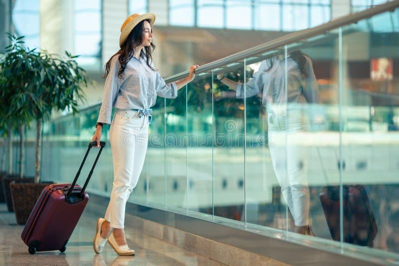 Jeune femme dans le chapeau avec des bagages dans l'aéroport international images stock