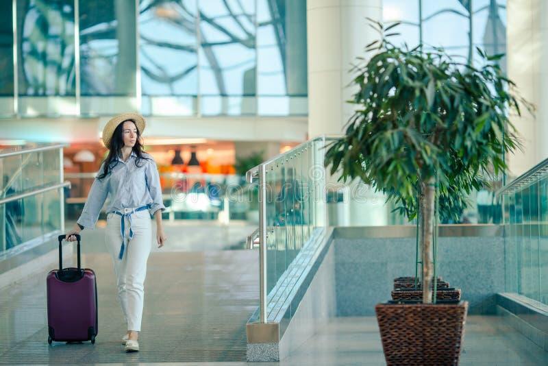 Jeune femme dans le chapeau avec des bagages dans l'aéroport international image libre de droits