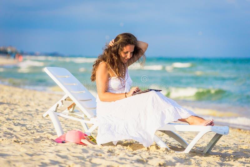 Jeune femme dans le chapeau avec le PC de comprimé à la plage photos libres de droits