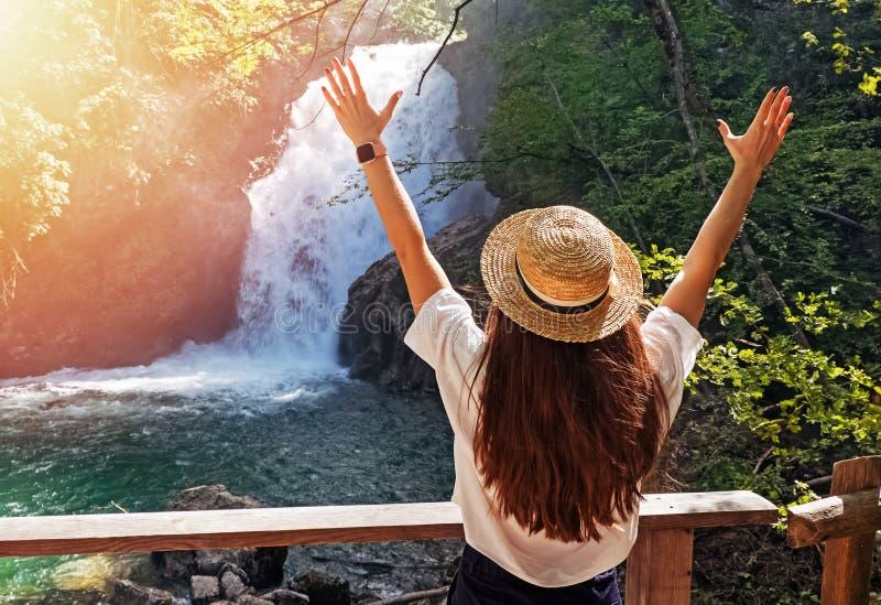 Jeune femme dans le chapeau de paille se tenant près de la cascade avec ses mains  E photographie stock