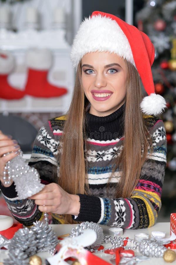 Jeune femme dans le chapeau de Santa se préparant à Noël se reposant au photos stock
