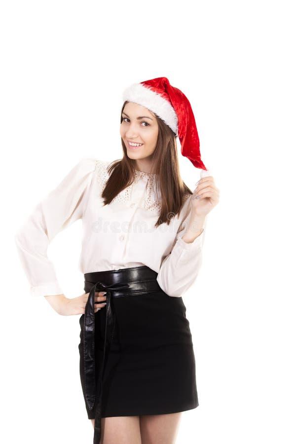 Jeune femme dans le chapeau de vêtement de bureau et de Santa Claus de rouge sur le Ba blanc photo stock