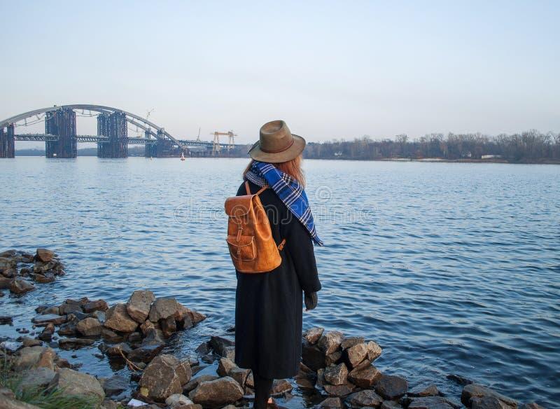 Jeune femme dans le chapeau et avec le sac à dos se tenant sur la rive, regardant le coucher du soleil ou l'horizon de lever de s photos libres de droits
