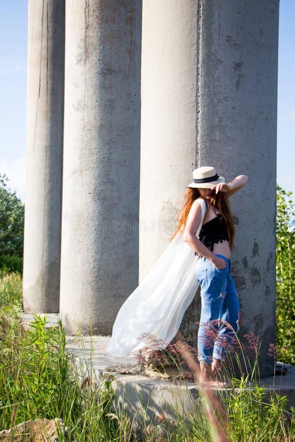Jeune femme dans le chapeau marchant en parc image stock