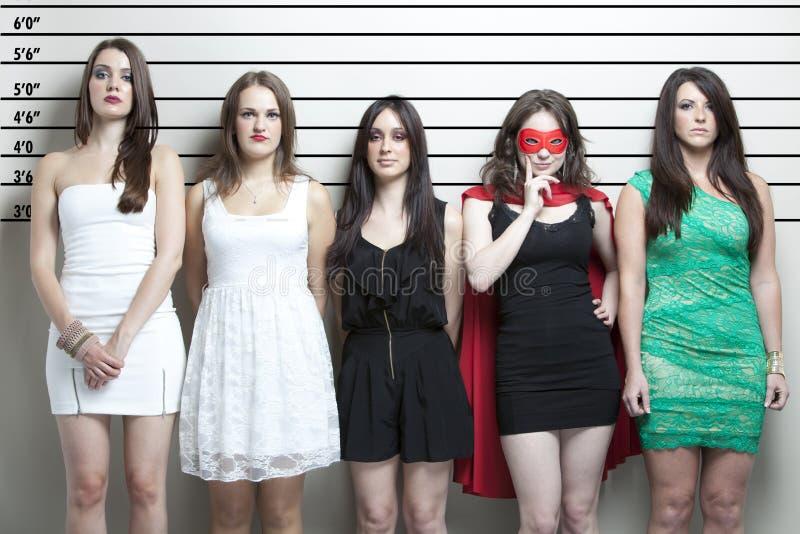 Jeune femme dans le costume de super héros avec des amis dans une ligne de police photo libre de droits