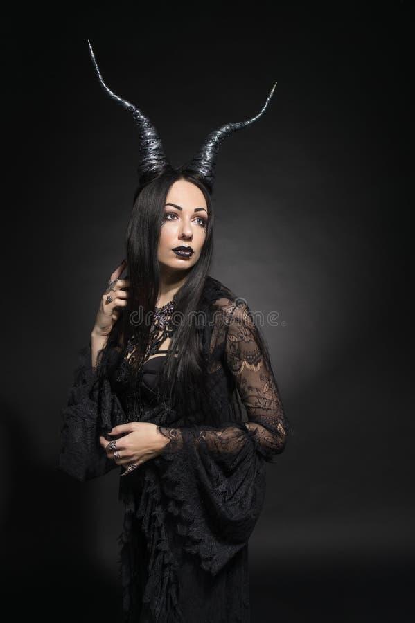 Jeune femme dans le costume noir d'imagination images stock